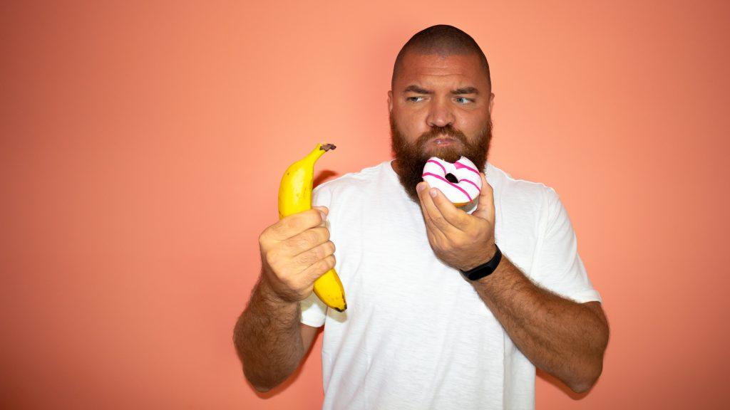 Mann hält eine Banane und einen Donut