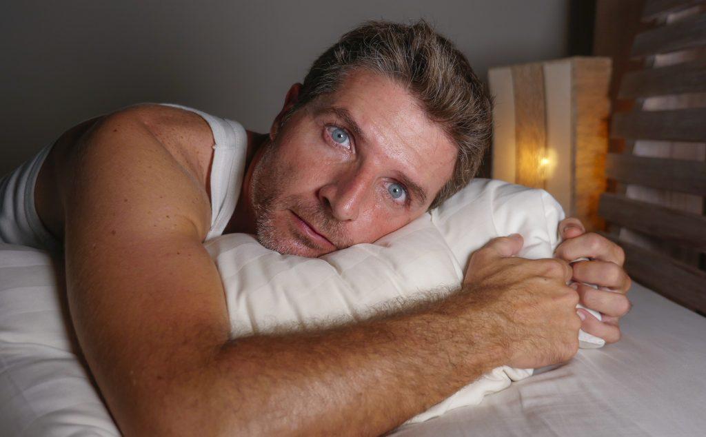 Mann liegt im Bett und schaut direkt in die Kamera