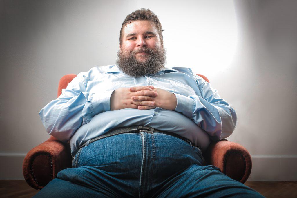 Dicker Mann auf Sofa