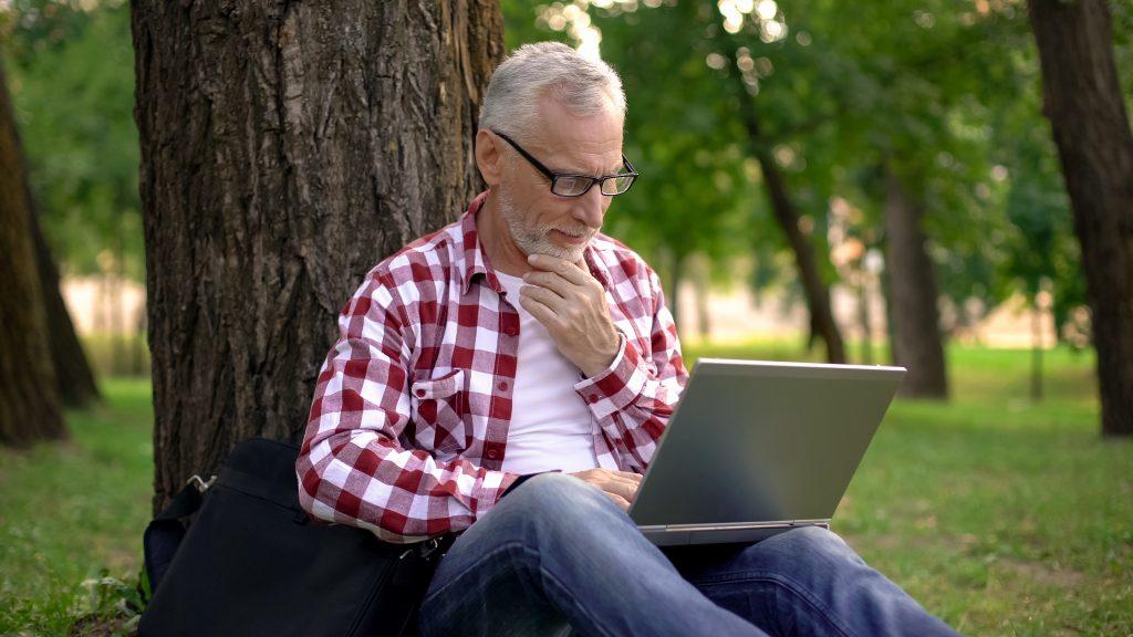 Mann sitzt mit Laptop im Wald
