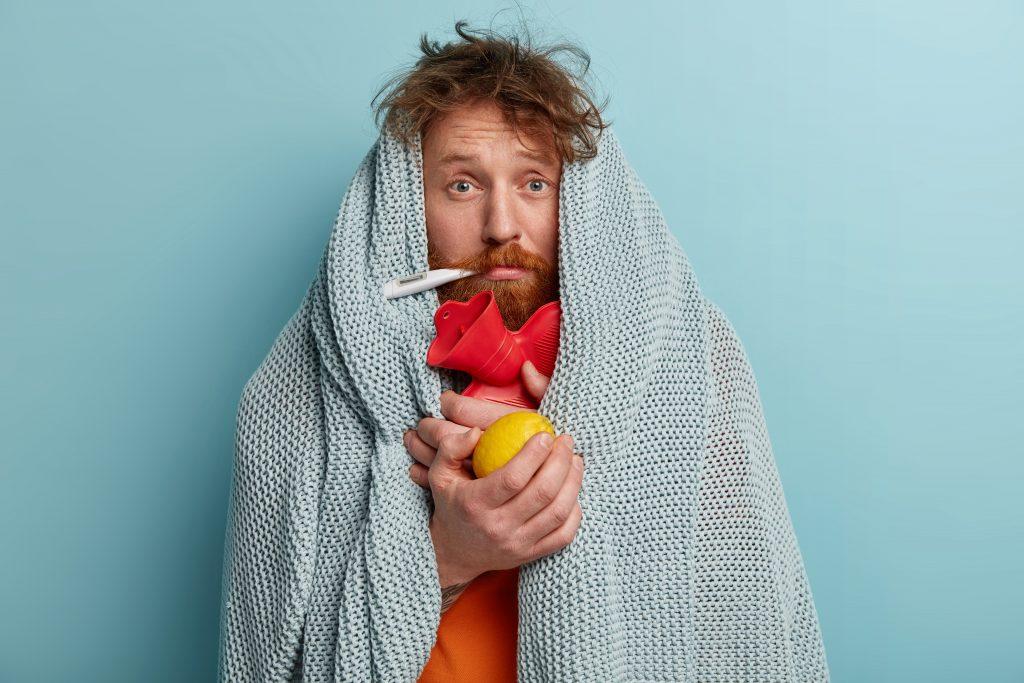 Mann mit Männergrippe in Decke gehüllt