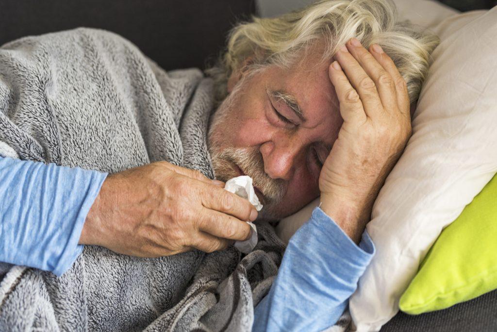 Senior mit Kopfschmerzen liegt im Bett