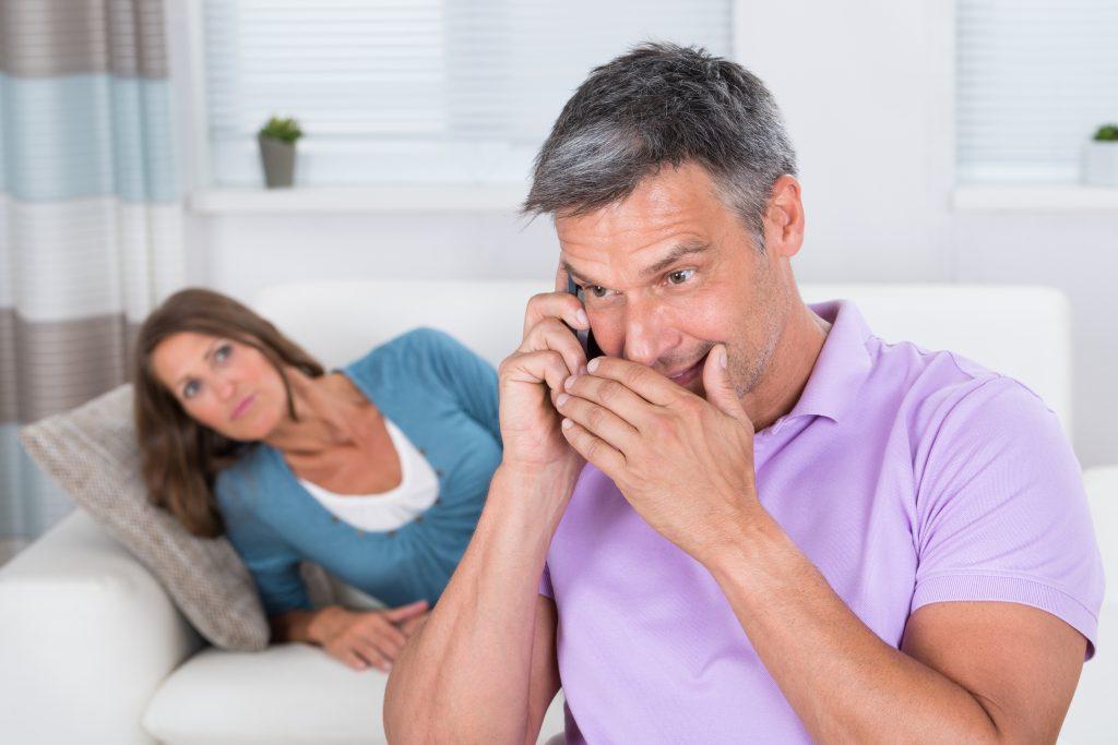 Mann telefoniert im Schlafzimmer mit der Ex