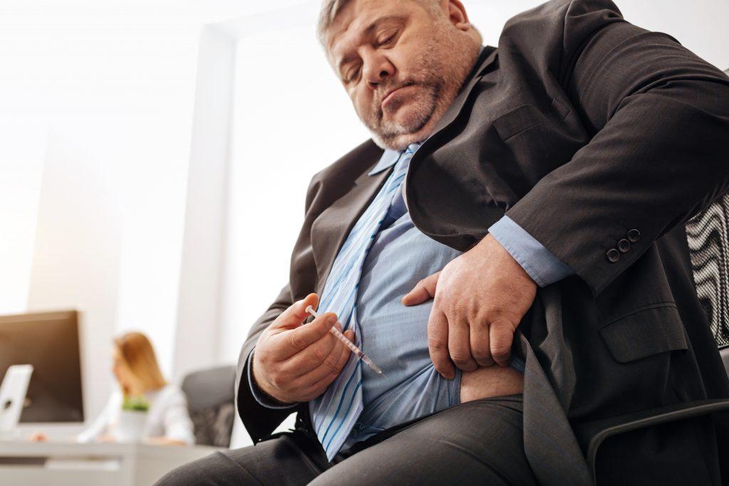 Dicker Mann spritzt sich Insulin